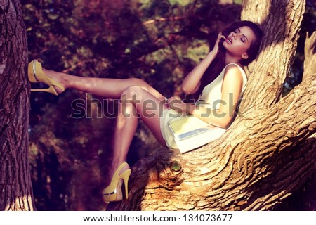 young sexy woman in yellow dress sitting on a tree branch. summer fashion portrait