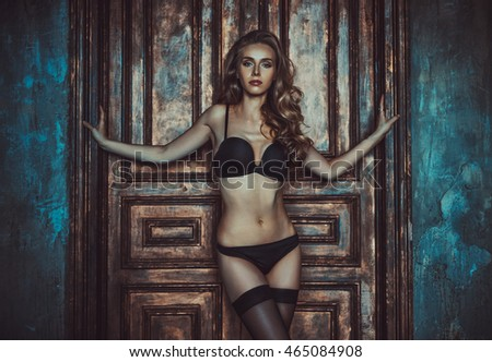 Young sexy woman indoors portrait on old wooden door background. Vintage film style colors.