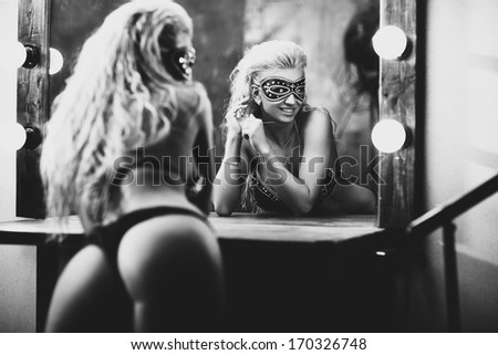 Young sexy woman looking at mirror. Black and white. - stock photo