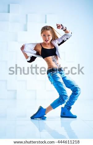 Young sexy woman modern dancer with tattoo on body in bright white interior - stock photo