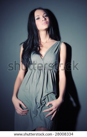 Young sexy woman on wall background. Contrast shadows effect. - stock photo