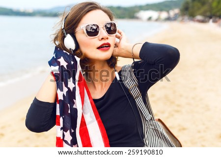 Young sexy woman posing at the beach listening music in her stylish big headphones, dancing and singing, travel with backpack, holding american flag.  - stock photo