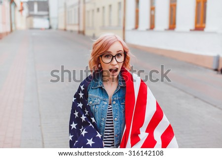 Young sexy woman posing at the city listening music, dancing and singing, travel with backpack, holding american flag. Positive crazy mood.Screaming,emotion  hipster girl - stock photo