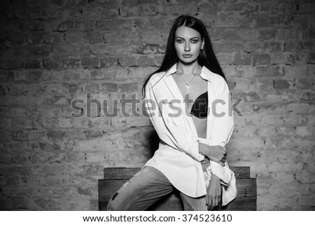 Young sexy woman posing in bra, shirt and jeans. Monochrome