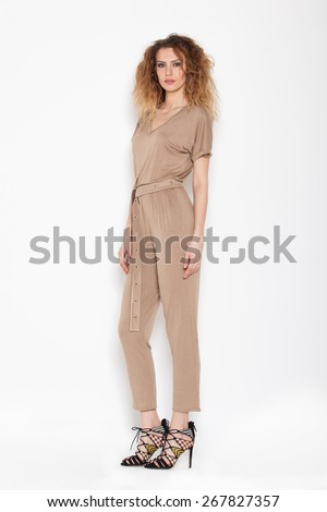 young sexy woman posing in brown rompers on white background