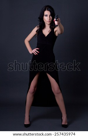 young sexy woman secret agent in black dress posing with gun over grey background - stock photo