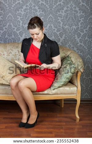 young sexy woman sits on a sofa and a reads green book - stock photo