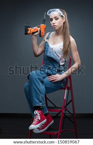 young sexy woman sitting at ladder and holding drill