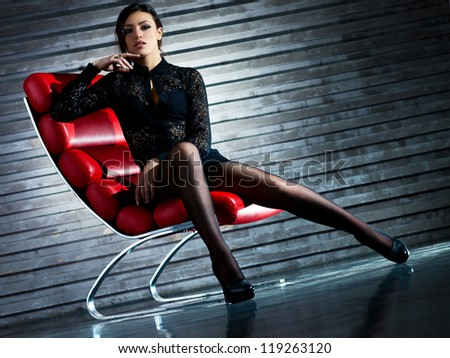 Young sexy woman sitting on chair. Camera angle view. - stock photo