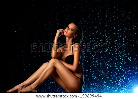 Young sexy woman sitting on rain background. - stock photo