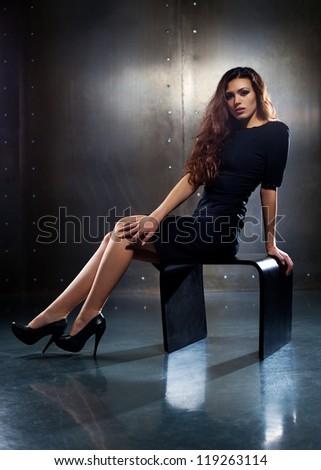 Young sexy woman sitting on stool. - stock photo