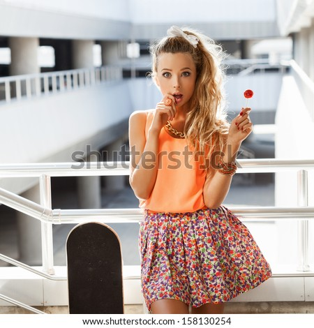 Young sexy woman sucking lollipop. Urban style. Outdoors, lifestyle. - stock photo