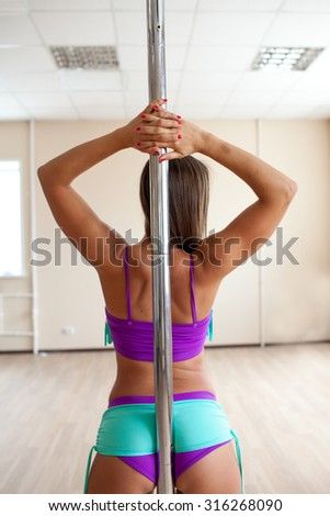 Young sexy woman traning pole dance in the classroom - stock photo