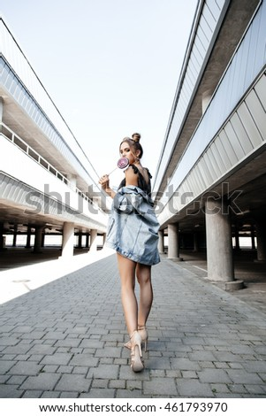 Young sexy woman walking on the street holding a lollipop. Outdoors, lifestyle portrait