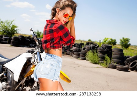 Young sexy woman,wear denim summer outfit and holding mirrored sunglasses,perfect glowing tan skin,attractive and,joy and happiness,trim,athletic figure,perfect female body,Motorcycles and drift show - stock photo