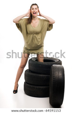 Young sexy woman with automobile tire and screaming - stock photo