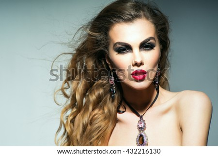 Young sexy woman with bare shoulders and bright makeup on pretty face with long curly hair and jewellery on grey background, copy space