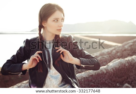 Young sexy woman with braids dressed in a silver dress and leather jacket. Fashion girl enjoying stunning views of the slope. Outdoors lifestyle portrait - stock photo