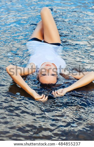 Young sexy woman with pretty face in wet white shirt laying in sea on river water with raised hands and slim legs outdoor