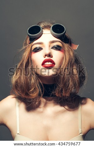Young sexy woman with red lips and bright makeup on pretty face in pilot retro glasses in bra on grey background