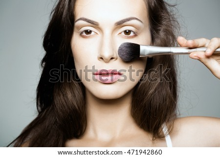 young sexy woman with soft skin on pretty face and long brunette hair holding fashionable makeup brush in studio on grey background