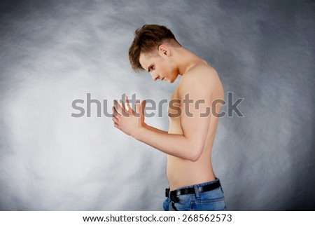 Young shirtless angry man trying to keep calm.