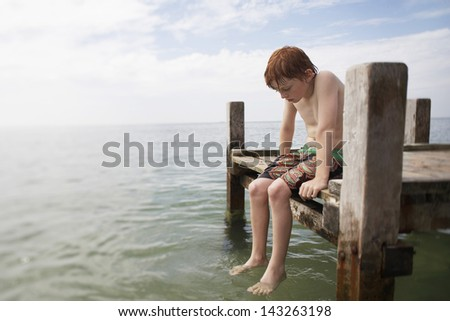Young shirtless boy sitting on jetty at beach - stock photo