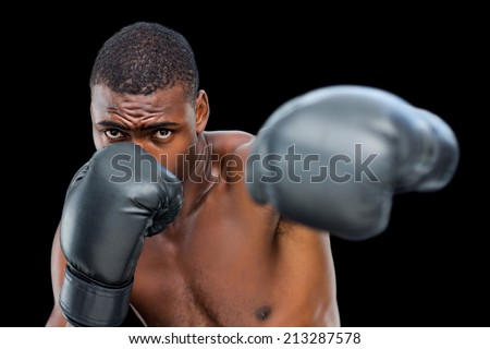 Young shirtless male boxer attacking with his left over black background