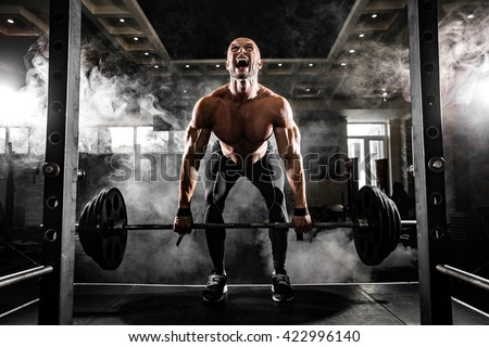 Young shirtless man doing deadlift exercise at gym. Screaming for motivation - stock photo