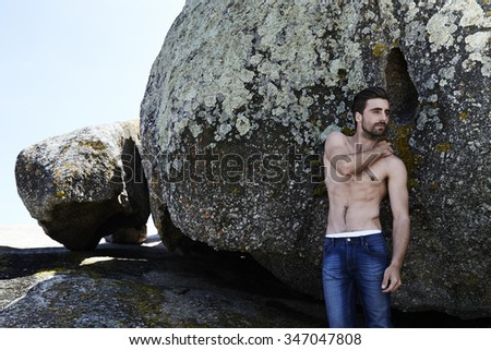 Young shirtless man standing on rock, looking away - stock photo