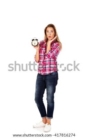 Young shocked woman holding alarm clock - stock photo
