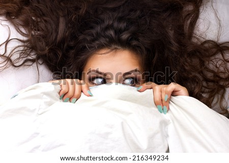 young shocking  woman with beautiful brown  dishevelled curls hair in the bed - stock photo