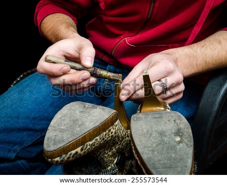 Young shoemaker gluing an old pair of shoes heel on traditional old fashioned way with brush - stock photo