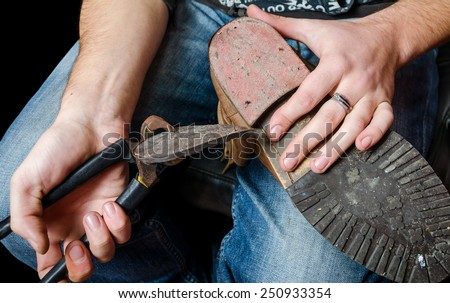 Young shoemaker repairing a old pair of shoes heel with a tool - stock photo
