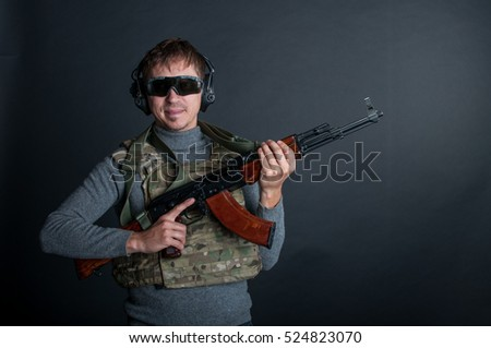 Young shooter with assault rifle in the hands