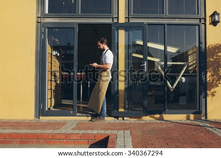 Young shop owner leaning in the doorway of his shop - stock photo