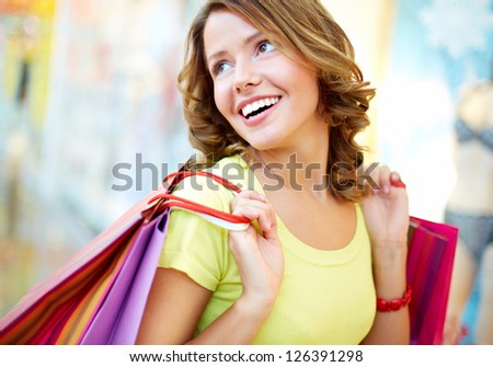 Young shopper being happy with her purchases and herself