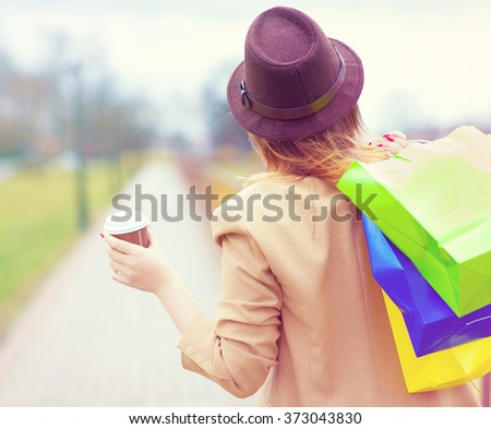Young  shopper woman wearing hat  glasses holding shopping bags and take away coffee walking in the street  - stock photo