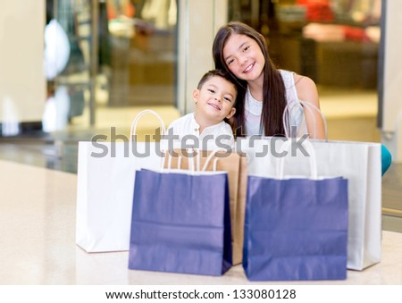 Young shoppers smiling at the shopping center - stock photo