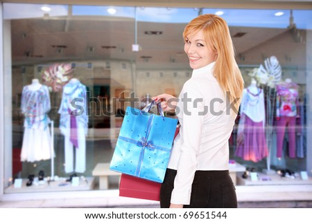 Young shopping woman in front of the shop