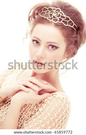 Young shy woman in a diadem of gold, isolated on white background.