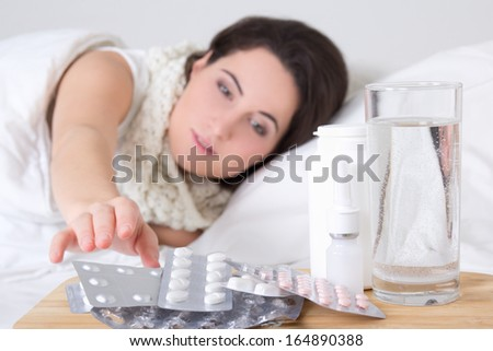 young sick brunette woman in bed and pills on the bedside table