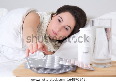 young sick woman in bed and pills on the bedside table