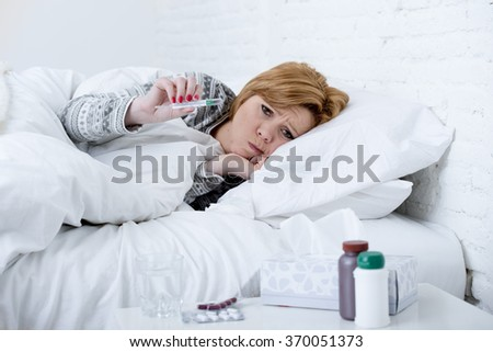 young sick woman in bed checking body temperature with thermometer looking bad , feverish and weak suffering winter virus like flu and influenza symptoms as headache and cold  in health care concept