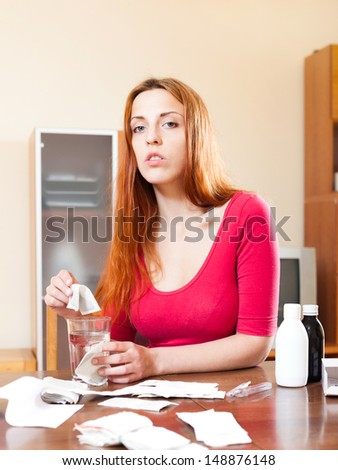 Young sick woman makes herself tea in living room