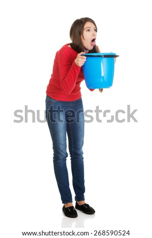 Young sick woman vomiting to bucket. - stock photo