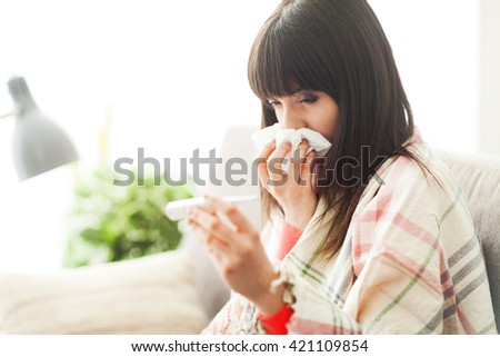 Young sick woman with cold and flu, she is blowing her nose and measuring her body temperature - stock photo