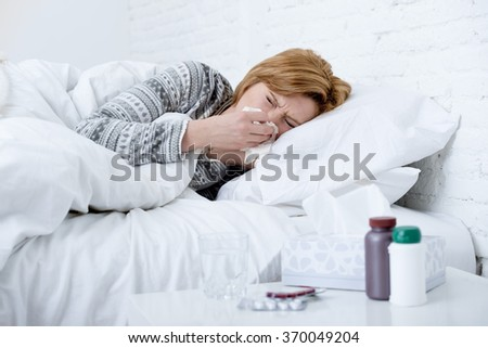 young sick woman with sneezing nose blowing in tissue lying on bed suffering winter cold and flu virus symptoms having medicines tablets and pills in illness and domestic health care concept - stock photo