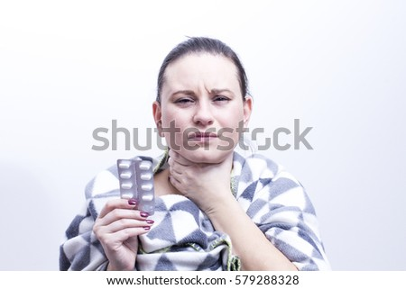 Young sick woman wrapped in blanket holding pills, has pain in throat, isolated