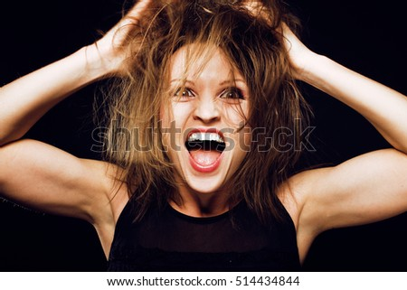 young silly crazy girl with messed hair making stupid faces on black background, lifestyle people concept